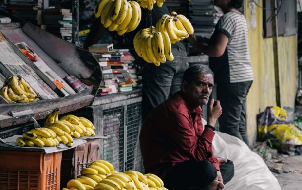 man sitting on chair near bananas