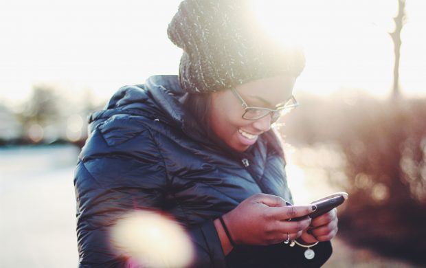 smiling woman wearing black coat using smartphone