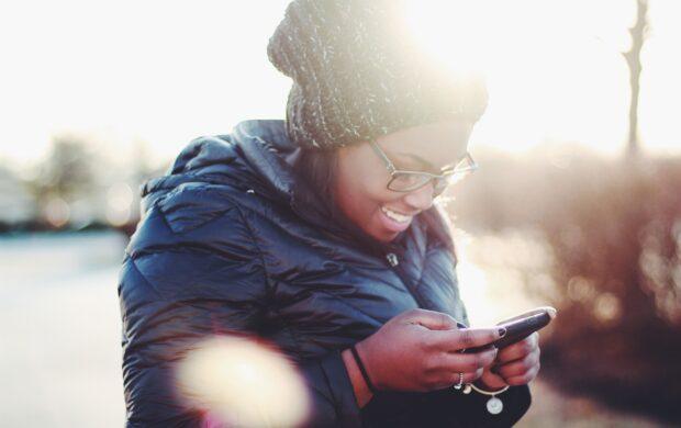 smiling woman wearing black coat using smartphone