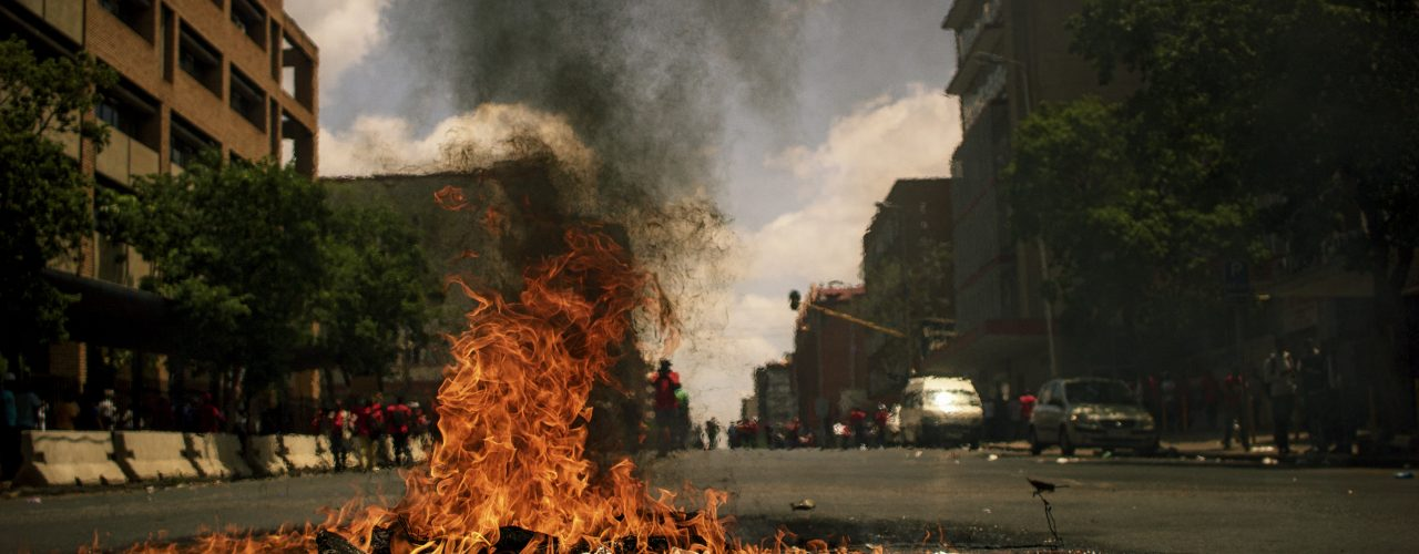 fire burning on the road with high rise buildings during daytime photography