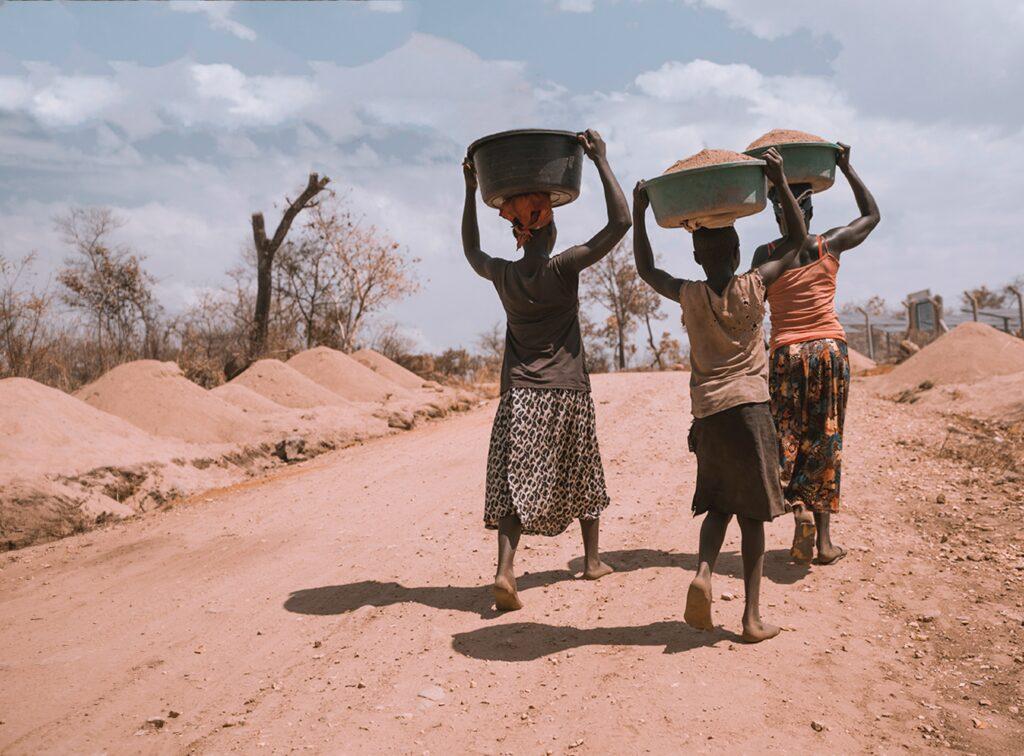 three women carrying basin while walking barefoot