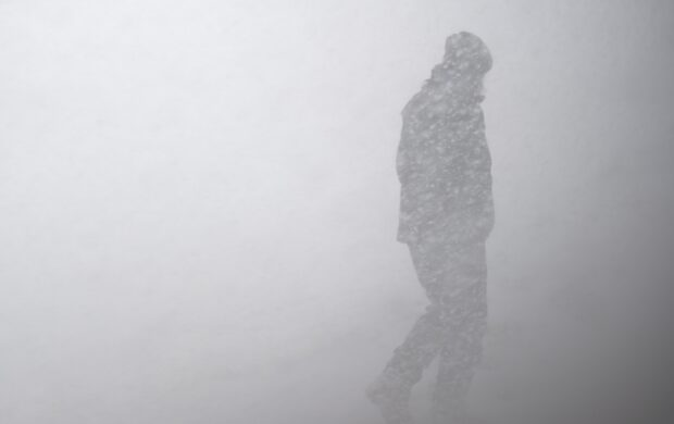 silhouette of man in snow storm