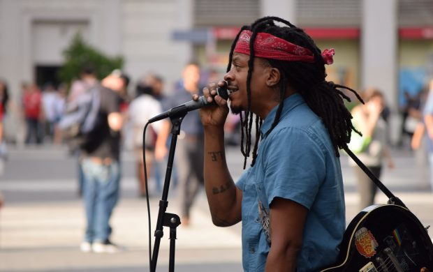 selective focus photography of man using microphone near people at daytime