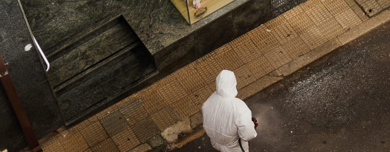 man in white thobe walking on sidewalk during daytime