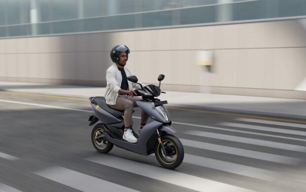 man in white dress shirt riding black motor scooter